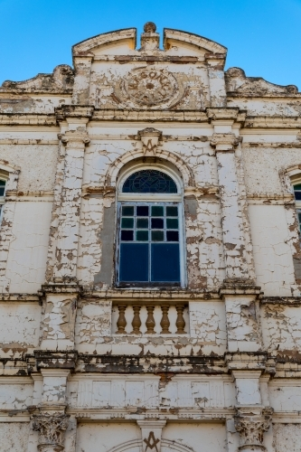 Center window of an old derelict building with weathered facade standing grand against a blue sky