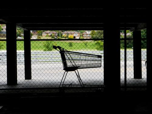 Lone shopping trolley in dark supermarket parking area