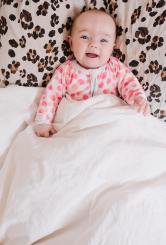 Cheeky little baby girl smiling from the bed.