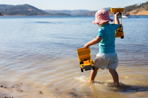 Child playing in the water with toys at Wyangala dam