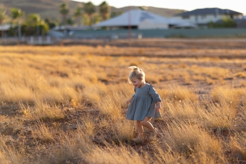 child running through dry grass with houses of town blurred in background
