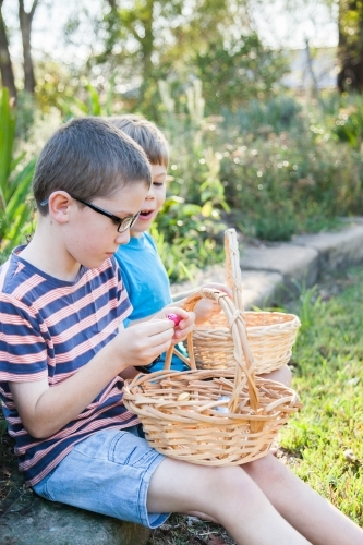 Two boys sitting eating chocolate eggs after Easter egg hunt