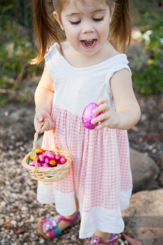 Happy little girl holding out pink Easter eggs