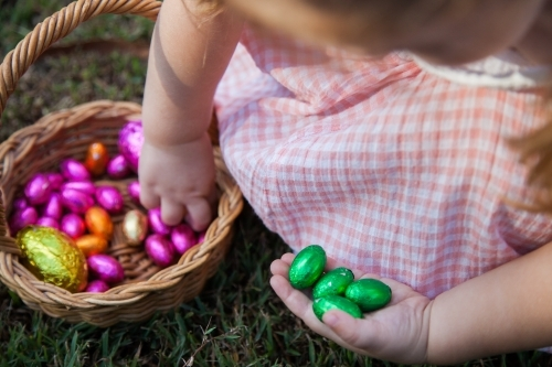 Close up of little girl taking coloured Easter eggs out of Easter egg hunt basket