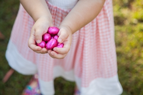 Childs hands hold out pink easter eggs