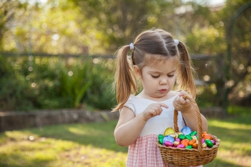 Cute little girl counting coloured Easter eggs in basket