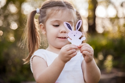 Happy little girl holding a homemade Easter bunny in the garden