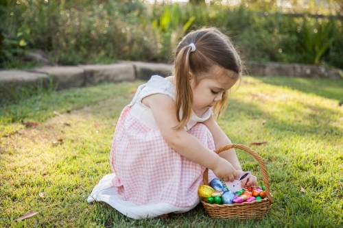 Child in garden putting Easter bunny in egg basket