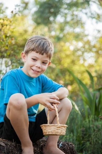 One young boy holding cane basket ready for Easter egg hunt