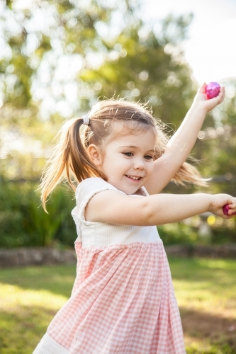 Happy three year old child spinning with Easter eggs she found