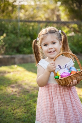 Happy kid holding basket of bright coloured Easter eggs found on an Easter egg hunt