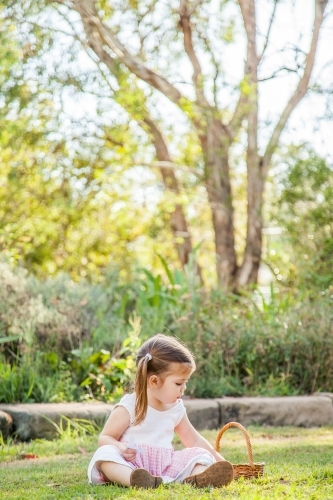 Little girl sitting on green grass in the garden with basket