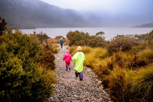 Children in bright rain jackets running down path on overcast day