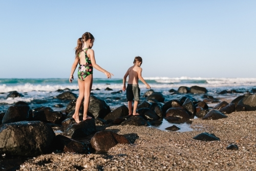 Children playing at the beach and climbing rocks