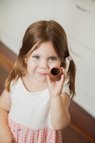 Child holding up hollow chocolate Easter egg she is eating
