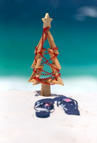 Christmas at the beach, sun, surf and leisure. A pair of thongs and small driftwood Christmas tree