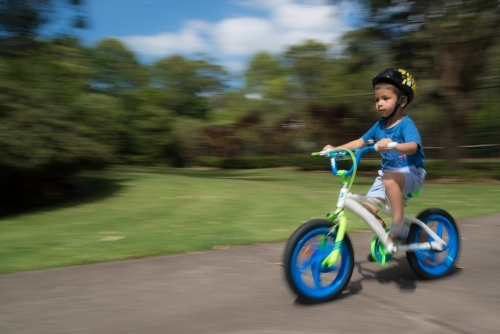 4 year old mixed race boy learns to ride his new bike for the first time. With motion blur