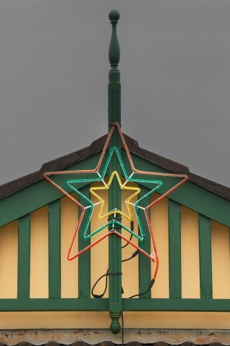 Christmas star decoration neon light on house gable roof