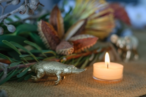 Christmas table arrangement with native flowers, tea light and gold platypus ornament