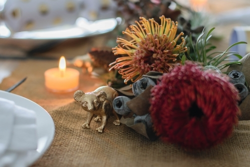 Christmas table setting with native flowers, candle and gold koala ornament