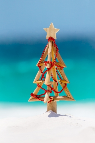 Christmas tree on idyllic white sandy beach with ocean background blur
