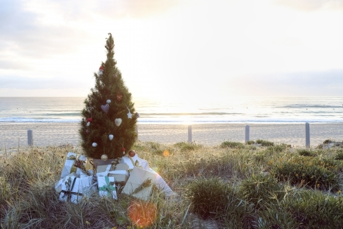 Christmas tree with presents on beach at sunrise