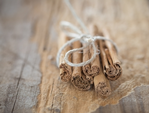 cinnamon stick tied in a bunch with string on wooden board