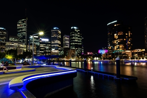 City lights with sky line, reflections in water and leading lines