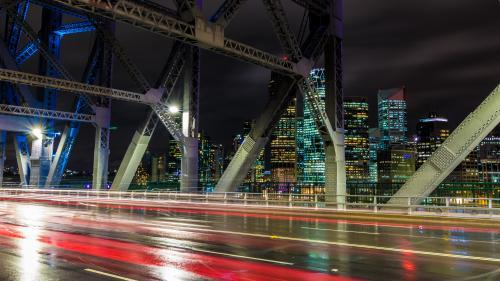 City skyline from bridge at night with traffic light trails