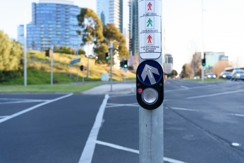 City traffic concept: Pedestrian press to go button at intersection, urban background