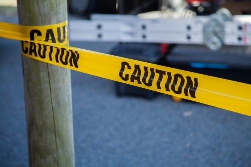 Caution tape around a post with ladder behind