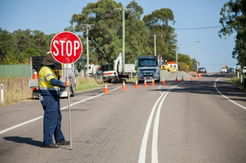 Worker in hi-vis holding roadwork stop sign