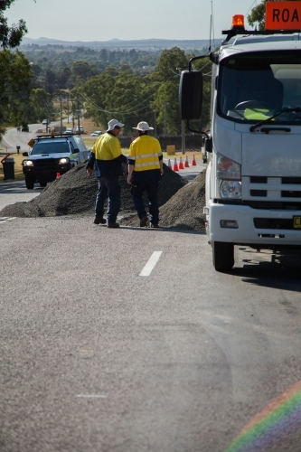 Two workers about to begin resurfacing road work