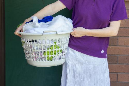 Young woman holding a basket of wet washing