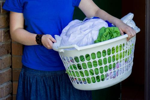 Young lady holding a basket of wet washing