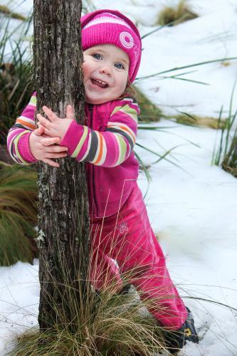 Little girl standing in snow hugging a tree