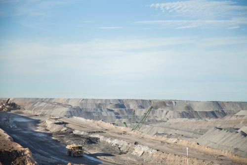 Dump trucks filling up with overburden and carting it through open cut coal mine
