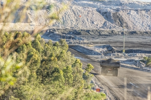 Distant truck carting coal in open cut mine