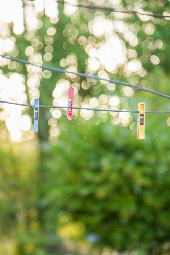 Three coloured clothes pegs hanging on an empty line with bokeh background