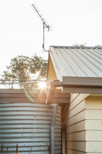 Sunlight shining past shed and rainwater tank