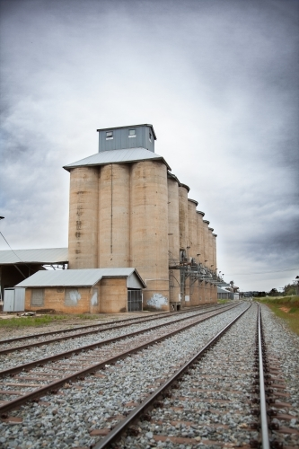 Wheat silo infrastructure beside a train line on an overcast day