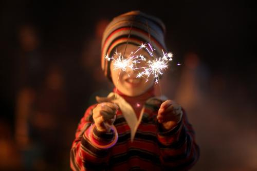 Little boy waving sparklers on a bonfire night