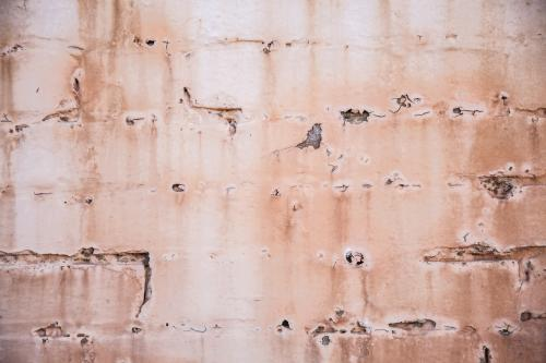 Paint peeling from faded pink brick wall