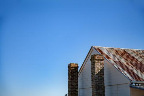 Rusty roof and stone chimney of old building against blue sky