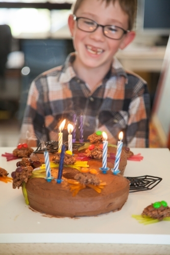 Child smiling behind number eight spider birthday cake