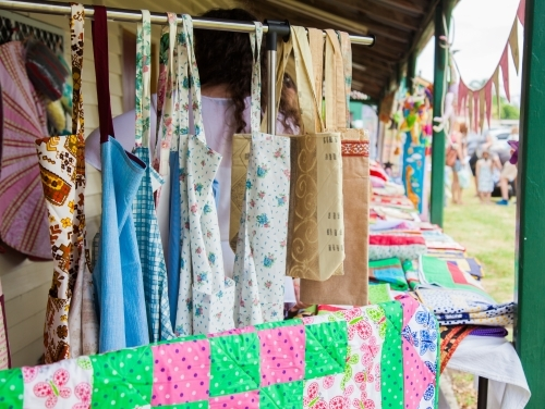 Quilted items and kitchen aprons for sale at a market stall