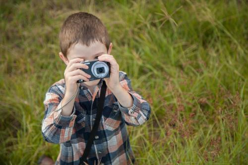 Young boy taking photos with a point and shoot camera