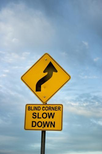 Blind corner slow down road sign against clouds