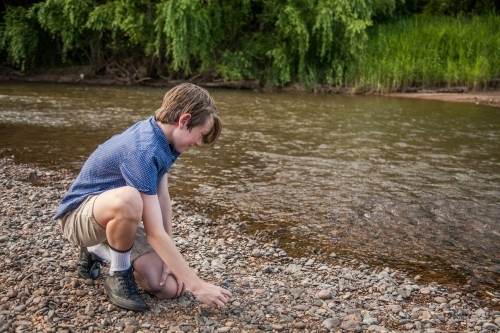 Young boy skimming stones beside a river