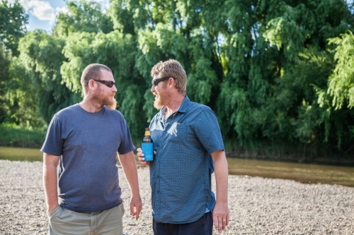 Two blokes drinking a beer together by the river